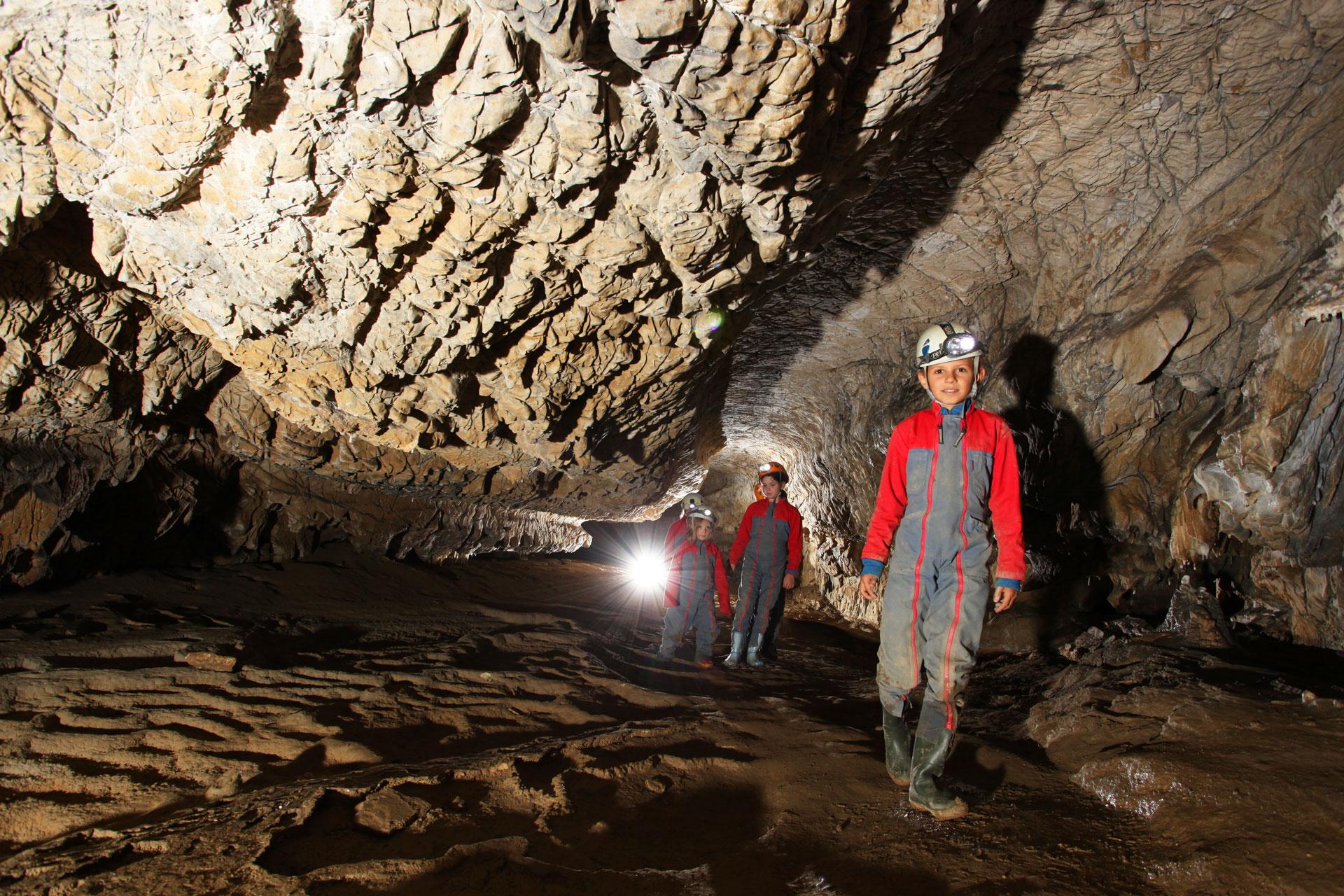 Spéléologie en Ariège, enfants dans une galerie de la grotte de Vicdessos en Ariège Pyrénées - Vertikarst ©Kasia